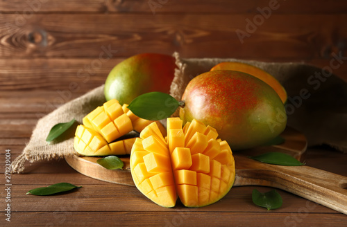 Photo Board with tasty fresh mango on wooden table