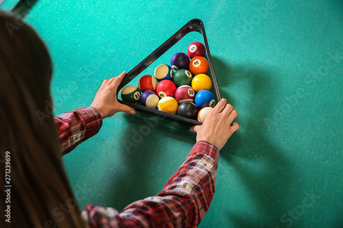 Fotografie, Tablou  Young woman playing billiard in club