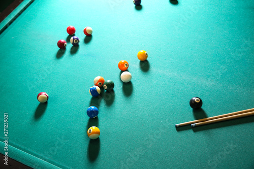 Fotografie, Obraz  Billiard balls with cues on table in club