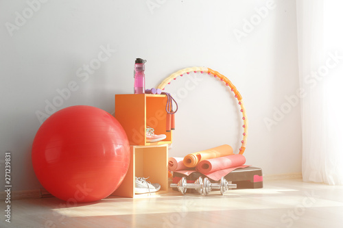 Fotografia Set of sports equipment with fitness ball near light wall