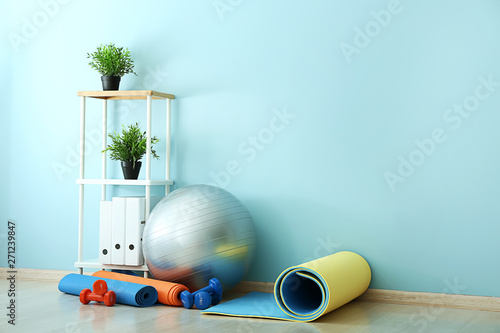 Foto Set of sports equipment with fitness ball near wall