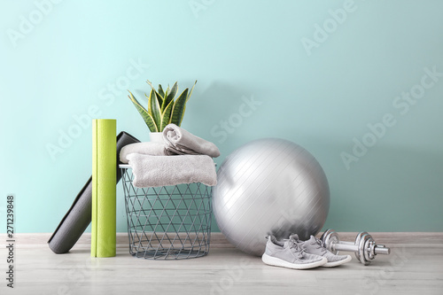 Obraz na plátně Set of sports equipment with fitness ball, towels and shoes near wall