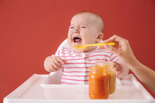 Crying Little Baby Eating Food On Color Background