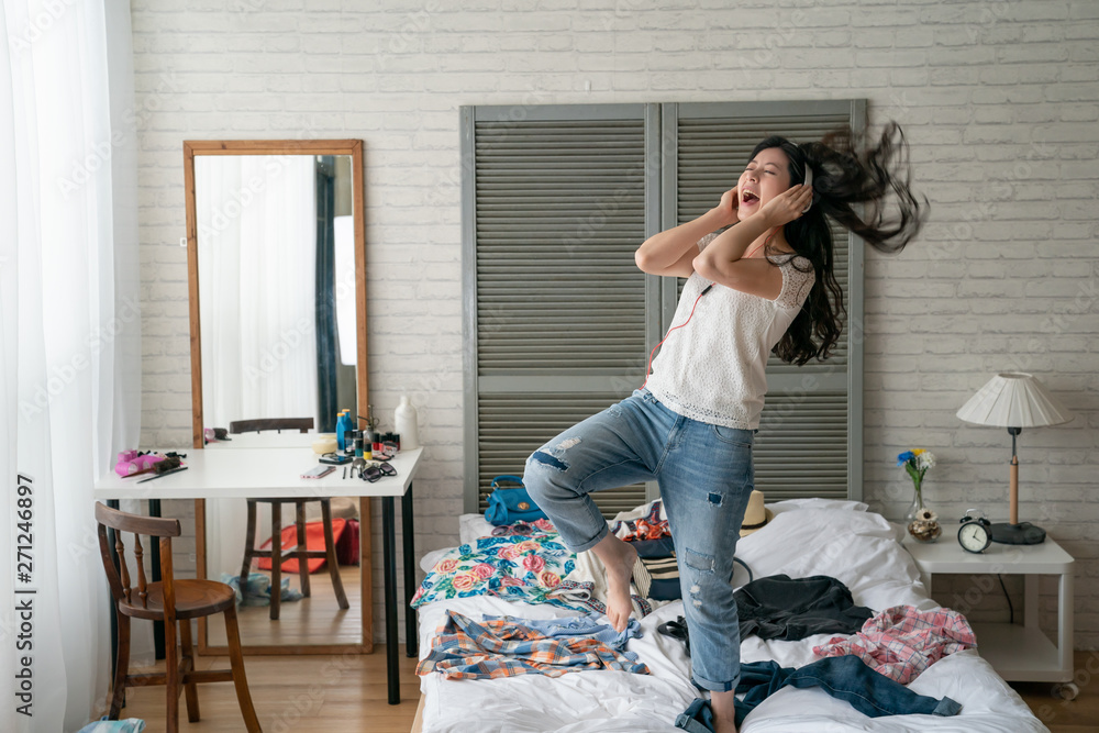 Fototapety, obrazy: Excited woman listening to music and dancing in home bedroom. crazy funny girl wear headphones enjoy melody new songs on internet move body relax while packing prepared luggage with clothes on bed.