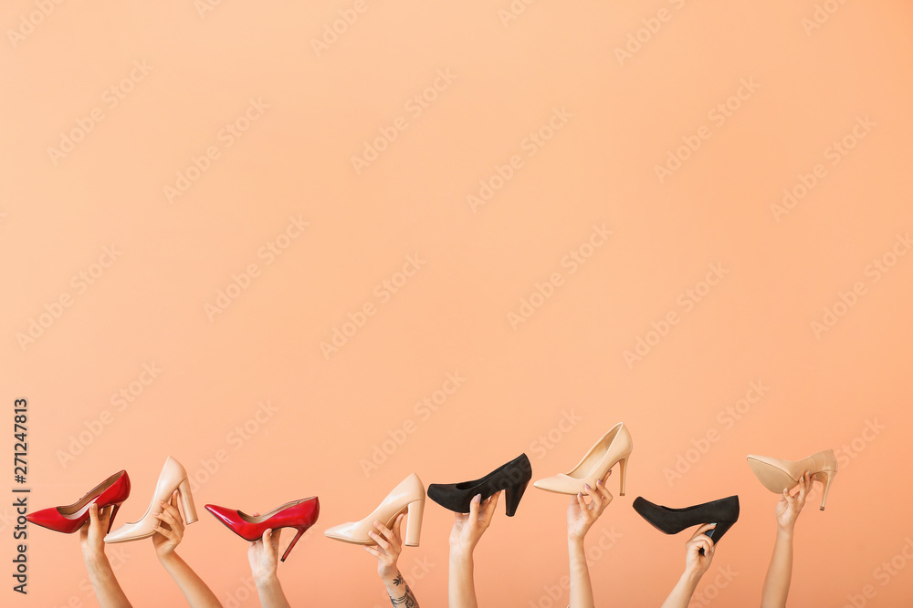 Fototapety, obrazy: Female hands with different stylish shoes on color background