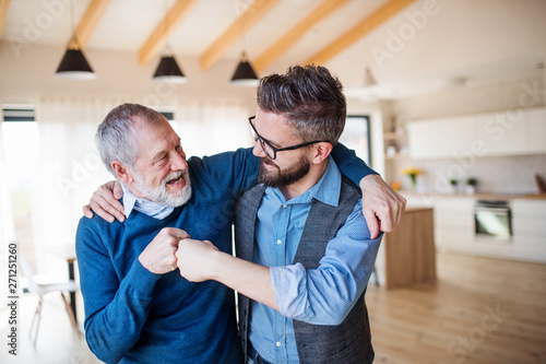 An adult son and senior father indoors at home, making fist bump. Fototapet