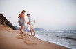 canvas print picture - Rear view of family with two toddler children walking on beach on summer holiday.