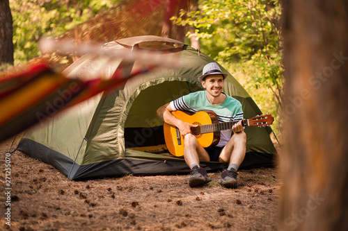 Fotografering  Happy young man camping and strum a guitar instrumental music to relax against background of forest sunset