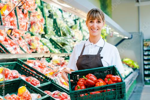 Verkäuferin im Supermarkt zeigt frisches Gemüse Fotobehang