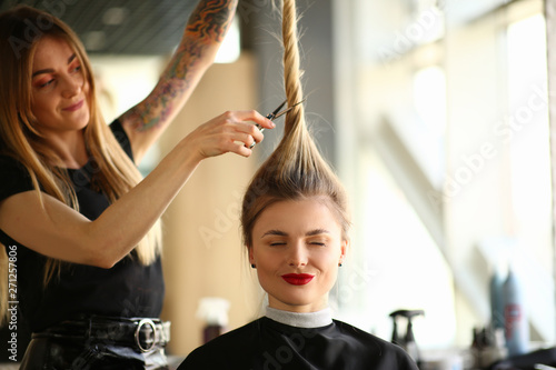 Valokuvatapetti Tattooed Stylist Cutting Hair of Closed Eyes Woman