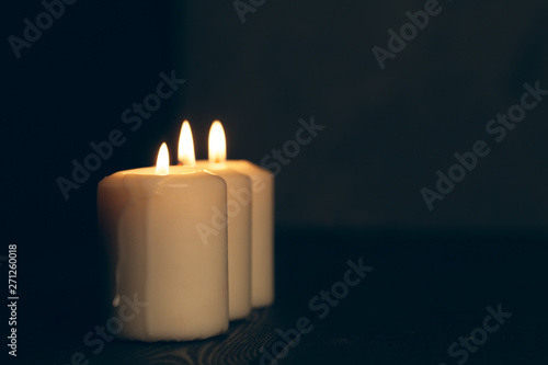 candles burning in darkness over black background Canvas Print