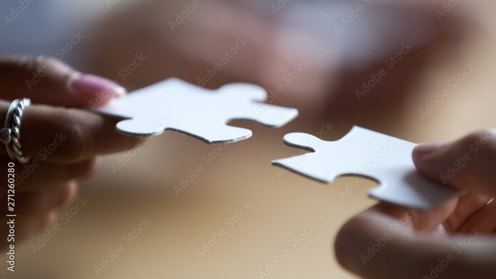 Fototapeta Close up multiracial business team members connecting puzzle pieces