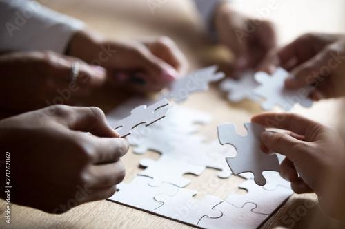 Close up members of multiracial team assembling white puzzle Wallpaper Mural