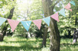 canvas print picture - Pastel bunting flags hanging among trees. Summer garden party. Outdoor birthday, wedding decoration. Midsummer, festa junina concept. Selective focus. Natural blurred background, sunny haze.