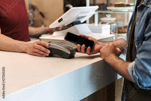Foto auf Leinwand Texturen Photo of european man paying cellphone in cafe while waiter holding payment terminal