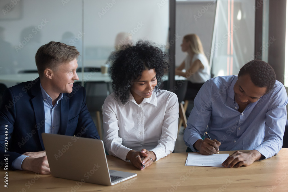Fototapeta African American man signing contract with business partners at meeting