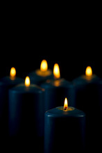 Lit Blue Candles On A Black Background