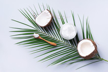 Coconut Oil And Ripe Coconuts, Tropical Palm And Monstera Leaves On Grey Background With Copy Space. Top View. Summer Creative Layout.
