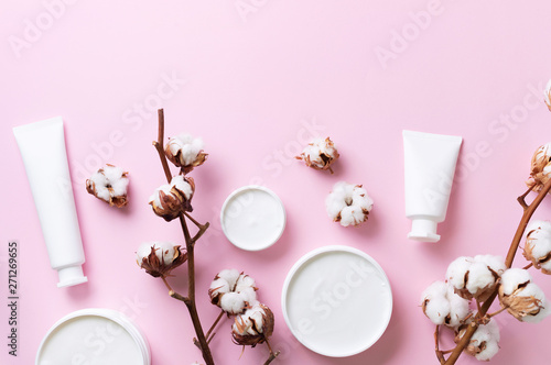 Staande foto Spa Fluffy cotton flowers, face cream, body butter on pink background with copy space. Cosmetics, beauty, spa concept. Top view. Flat lay