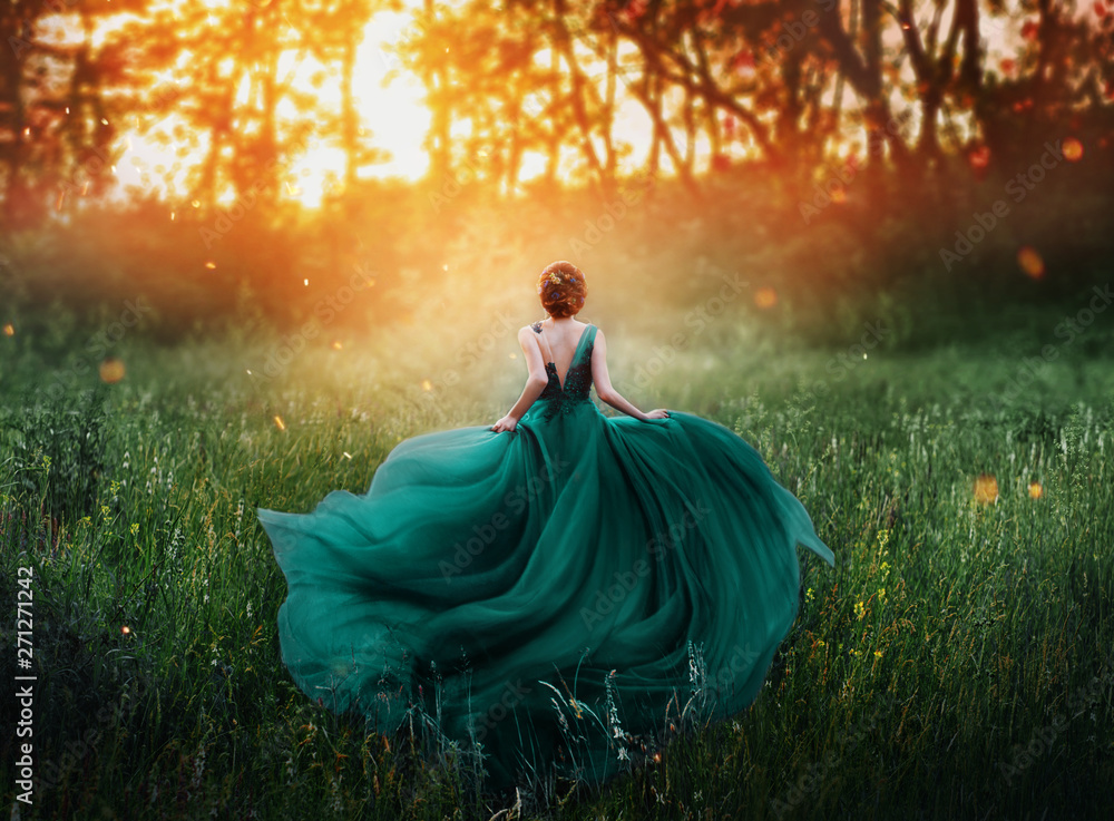 Fototapeta magical picture, girl with red hair runs into dark mysterious forest, lady in long elegant royal expensive emerald green turquoise dress with flying train, amazing transformation during fiery sunset