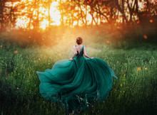 Magical Picture, Girl With Red Hair Runs Into Dark Mysterious Forest, Lady In Long Elegant Royal Expensive Emerald Green Turquoise Dress With Flying Train, Amazing Transformation During Fiery Sunset