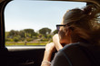 Leinwandbild Motiv Back shot of attractive blonde European woman wearing sunglasses sitting inside car with open window, enjoying road trip, looking out, admiring beautiful summer views. People and lifestyle concept