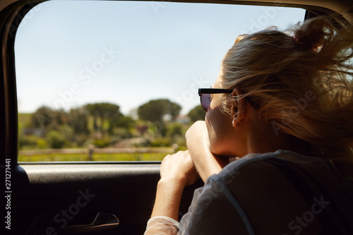Back shot of attractive blonde European woman wearing sunglasses sitting inside car with open window, enjoying road trip, looking out, admiring beautiful summer views Tablou Canvas