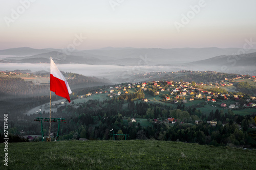 Waving Polish flag in the mountains above the village Фотошпалери