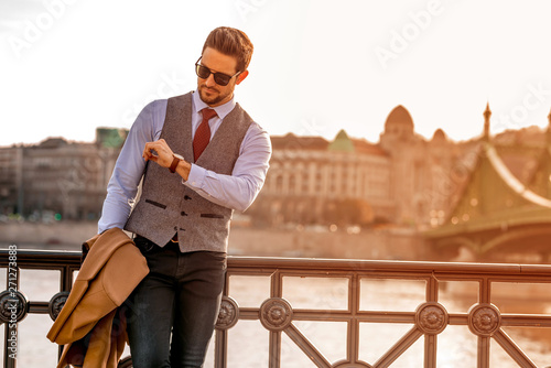 Obraz An elegant man standing next to a river and checking the time - fototapety do salonu