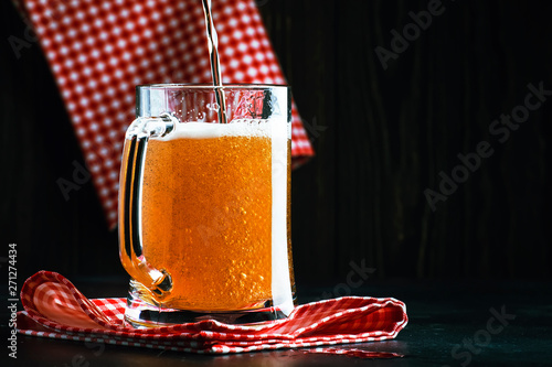 light beer in a little old-fashioned mug on old wooden table, selective focus