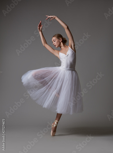 Photo Ballerina dancing in white dress. Color photo.