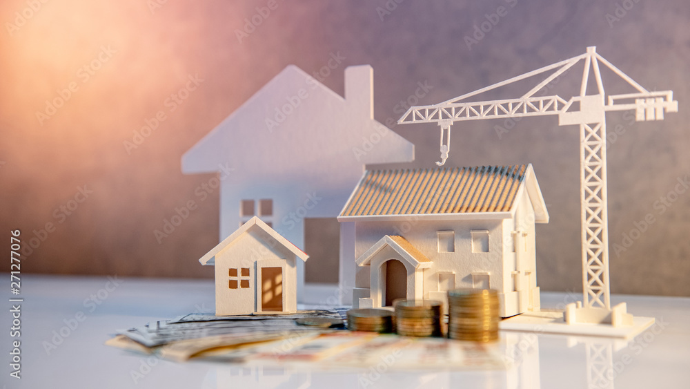 Fototapeta Real estate or property development. Construction business investment concept. Home mortgage loan rate. Coin stack on international banknotes with house and construction crane models on the table.