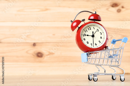 Poster Nature Small shopping cart with alarm clock on brown wooden table