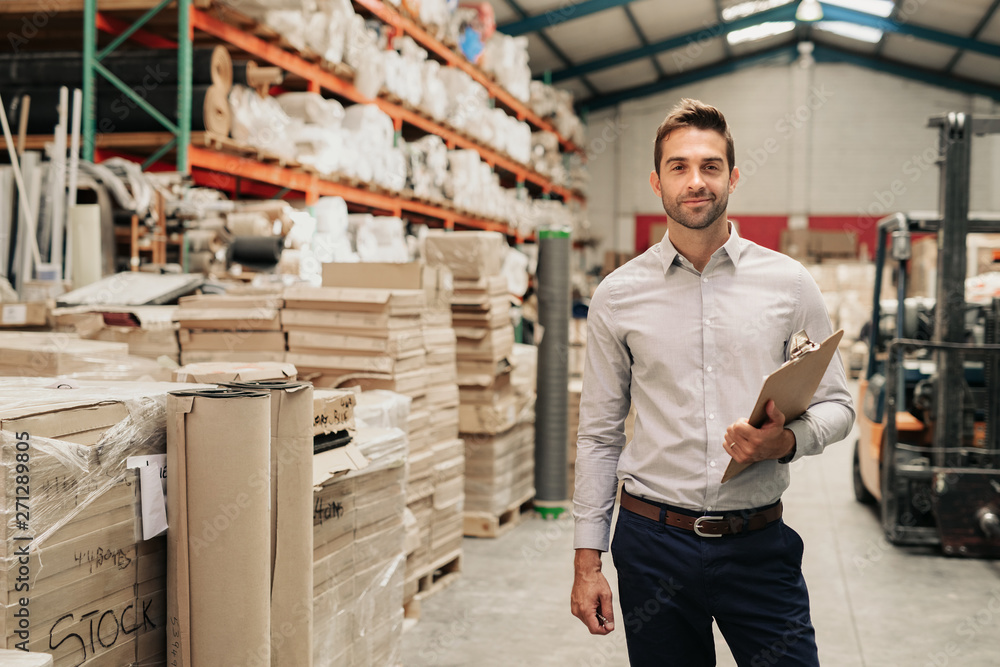 Fototapeta Smiling manager standing in his warehouse with a clipboard