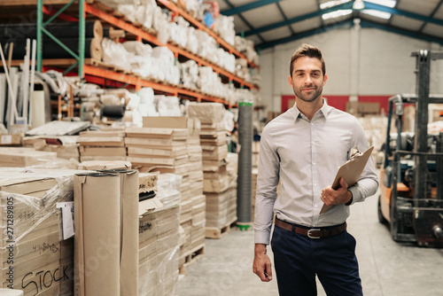Smiling manager standing in his warehouse with a clipboard