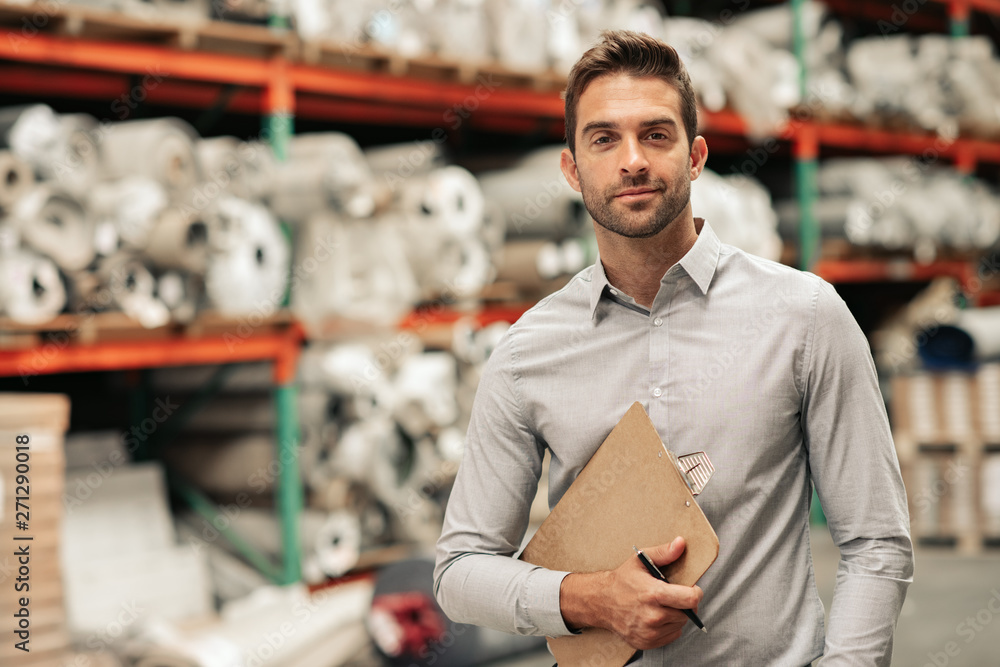 Fototapeta Manager standing with an inventory clipboard on a warehouse floor