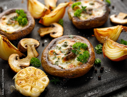 Fototapeta Baked portobello mushrooms stuffed with cheese and herbs on a black background, close-up. Vegetarian food obraz
