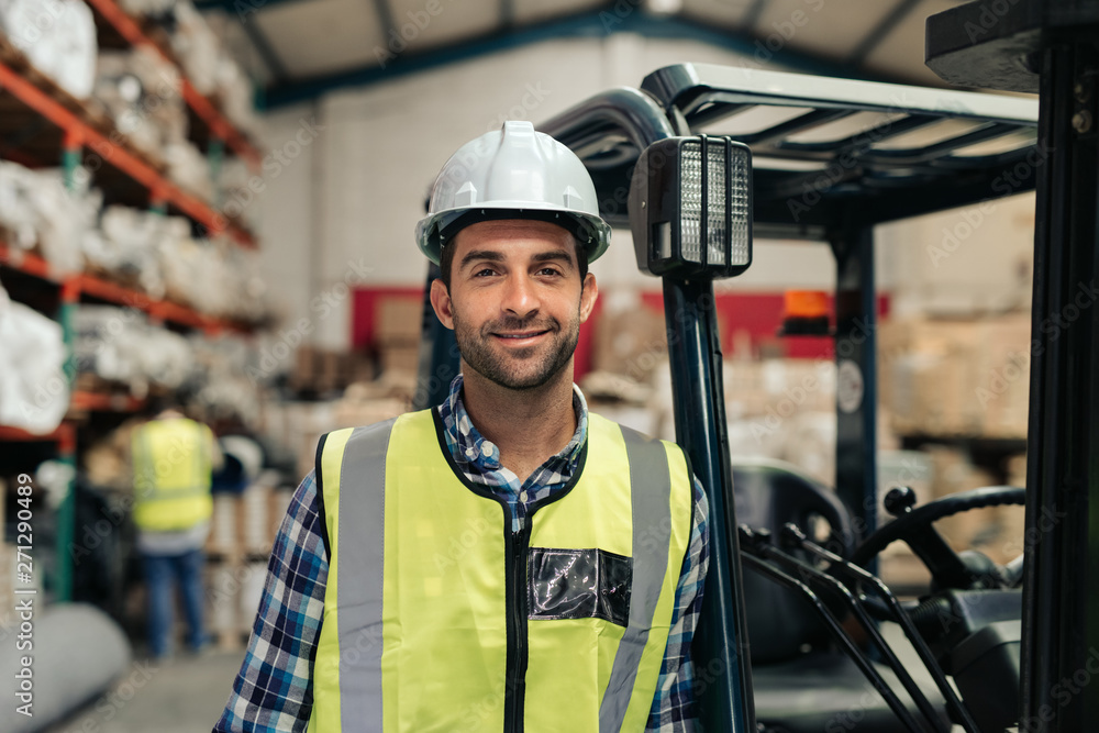 Fototapeta Smiling worker standing by his forklift in a warehouse