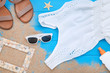 Fashion clothing with sunscreen and frame on blue wooden table