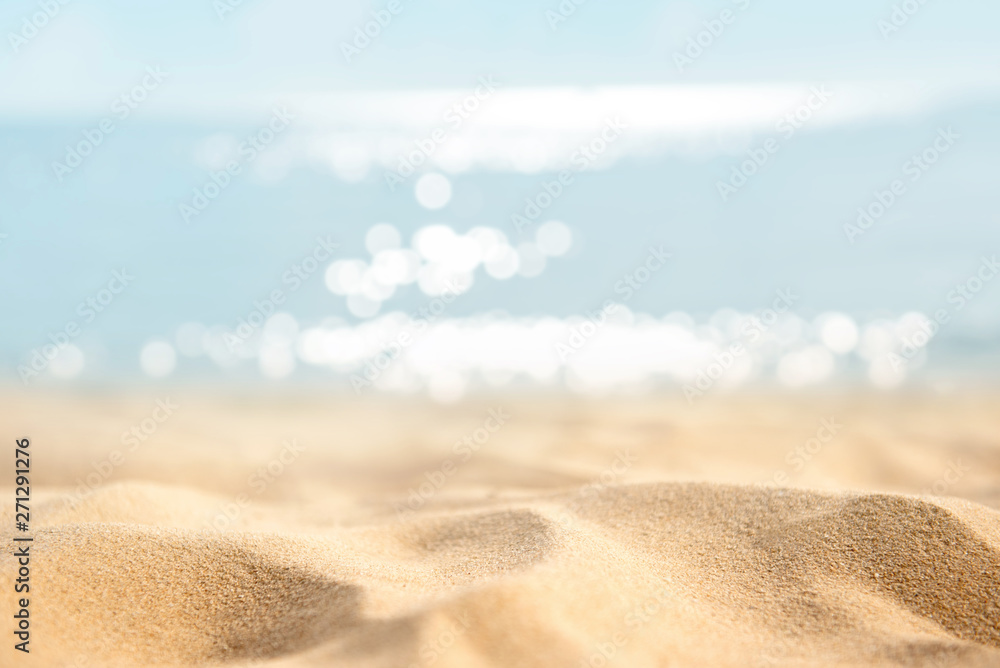 Fototapeta Summer tropical sand beach and bokeh sun light on sea background, copy space.