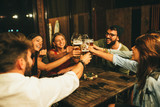 Group of friends drink beer on the terrace and toast during summer night - 271292635