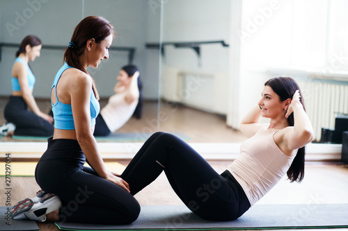 Personal trainer, teamwork, workout, perfect shape. Fit sporty woman doing sit-ups with fitness instructor support