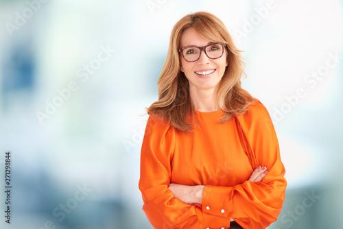 Photo Portrait of executive middle aged businesswoman looking at camera and laughing