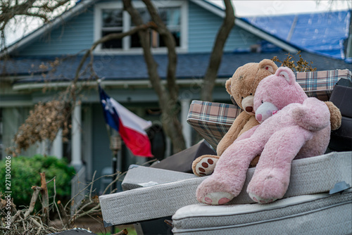 Fototapeta One Week After Hurricane Harvey in Front of destroyed home two teddy bears hold each other obraz