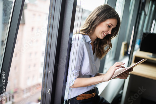 Happy woman manager holding tablet and standing in modern office - 271305641