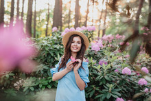 Beautiful Girl In Blue Vintage Dress And Straw Hat Standing Near Pink Flowers.