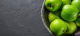Fresh juicy green apple in stainless steel colander on Dark grey black slate background