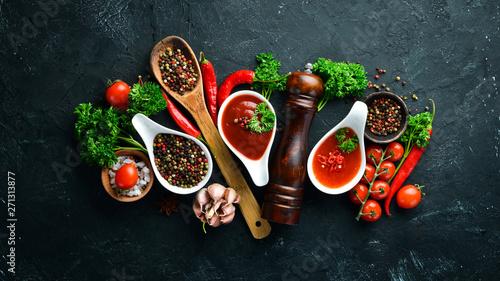 Cuadros en Lienzo A set of tomato sauces on a black stone background