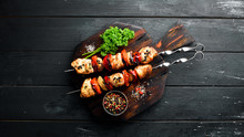 Chicken Shish Kebab With Onions And Tomatoes. Barbecue. On A Black Background. Top View. Free Space For Your Text. Rustic Style.