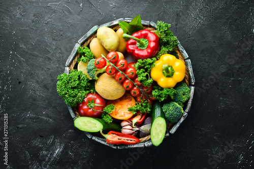 Fresh vegetables and fruits in a wooden box. Avocados, tomatoes, strawberries, melons, potatoes, paprika, citrus. Top view. Free space for your text. - 271315285